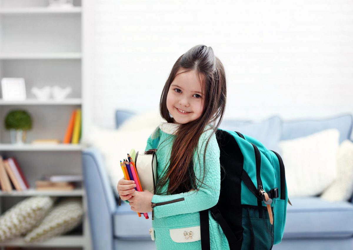 Little,Girl,With,Green,Back,Pack,Holding,Stationery,In,Living